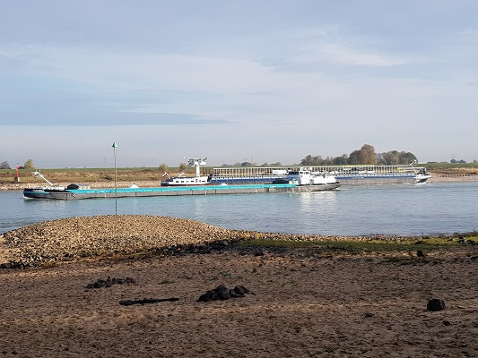 Wandelen over klompenpad Doddendaelpad bij scheepvaart over de Waal in Beuningen
