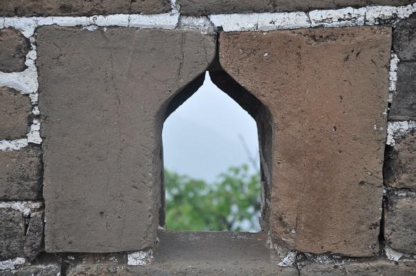 Kijkgat in muur tijdens een wandeling over de Chinese Muur in China