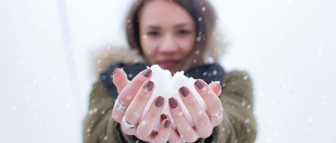 Woman holding a snowball. The snowball represents one of the main methods for debt repayment: the snowball method.
