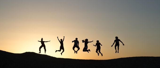 Silhouette of 6 friends jumping in the air during sunrise