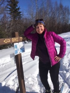 Author Laurie Robertson leaning on a bike trail sign in winter