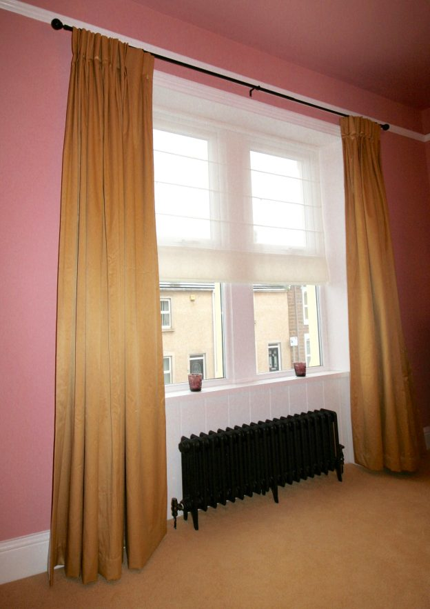Gold curtains in pink bedroom and black Victorian style cast iron radiator