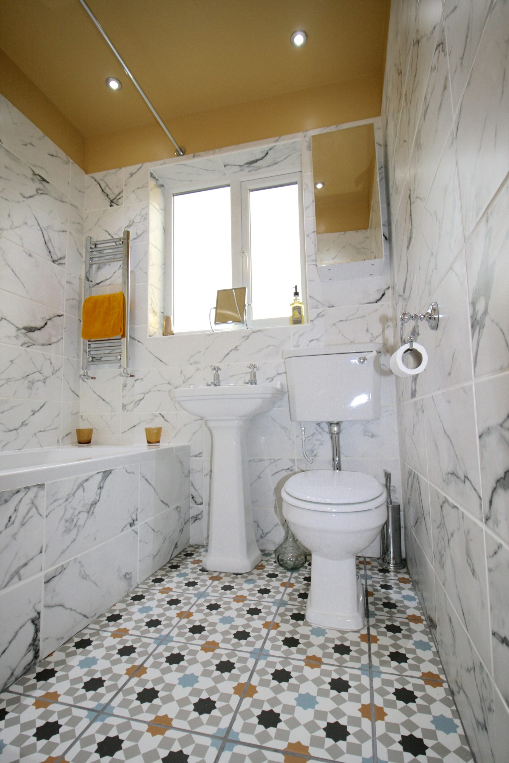 Bathrooms - Bijou bathroom with bold encaustic floor tiles and large marble wall tiles