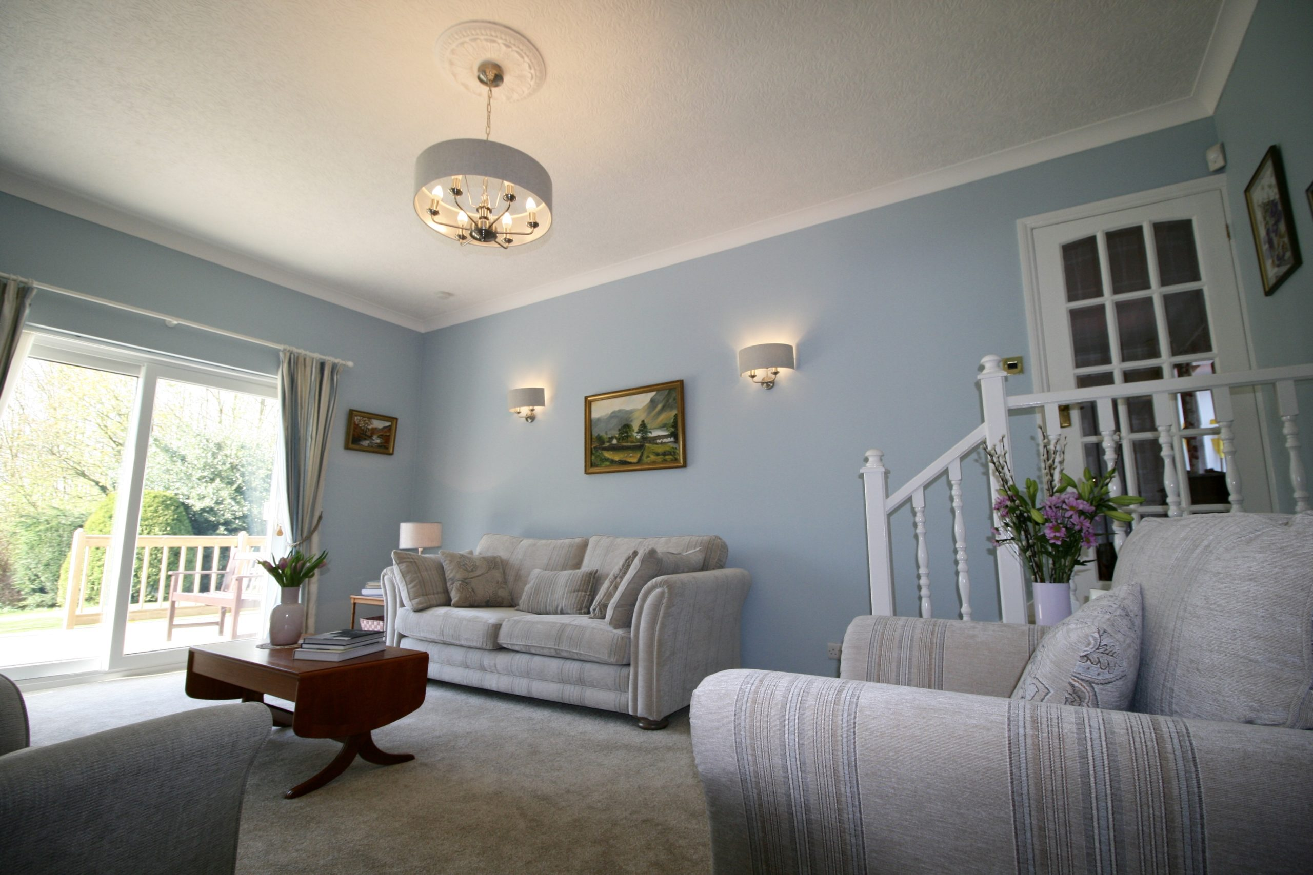 Living room with Valspar Windblown blue and linen colour scheme with pale pink accents and Laura Ashley soft furnishings