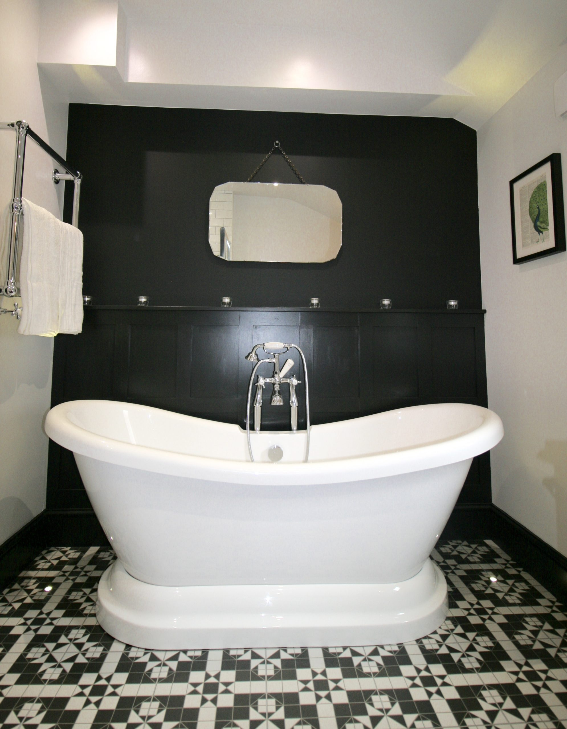 Bathroom - double ended slipper bath against a black panelled wall and lit from below