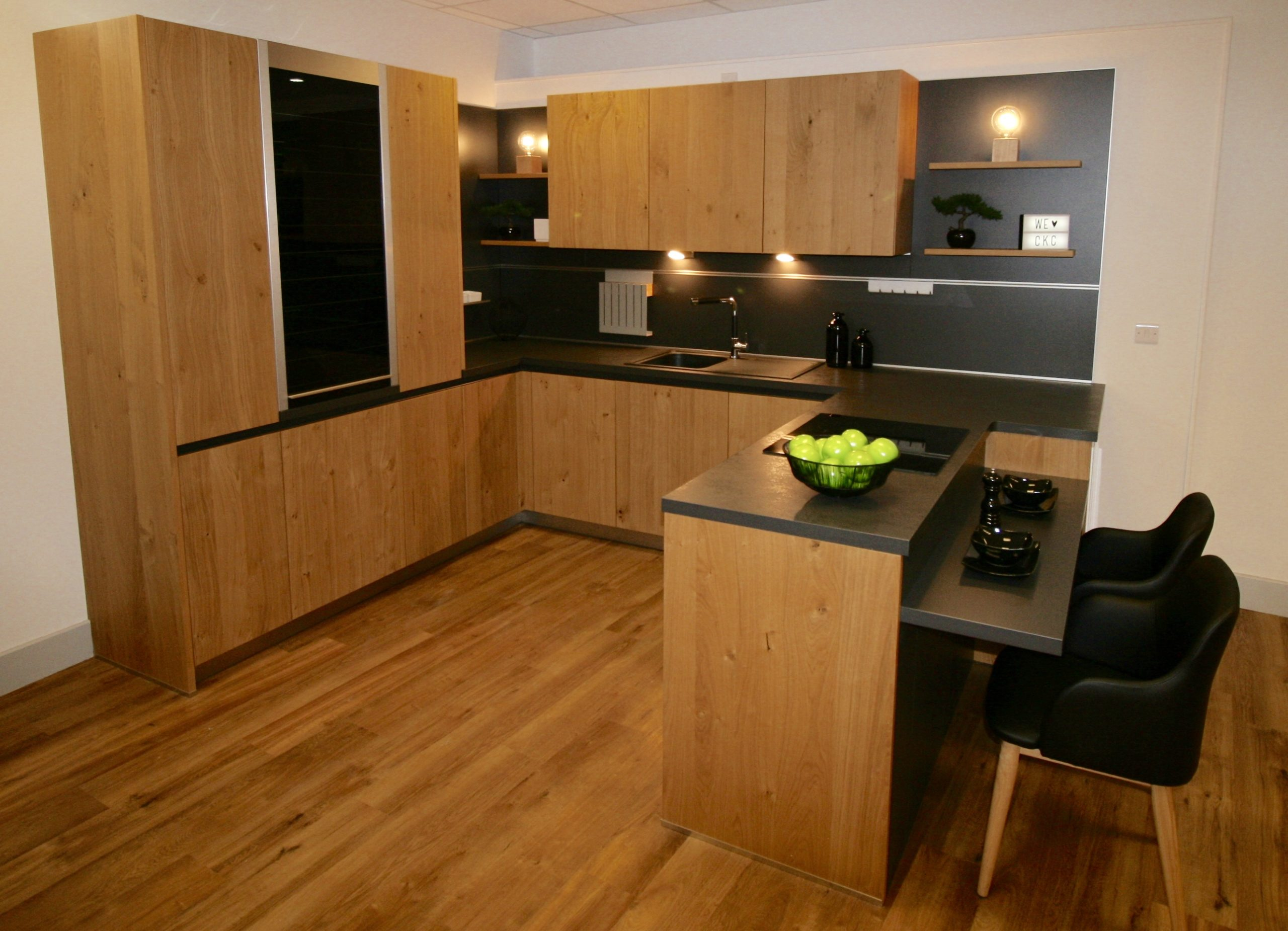 Schuller Bari kitchen with solid wood doors and black laminate worktops and wall panels