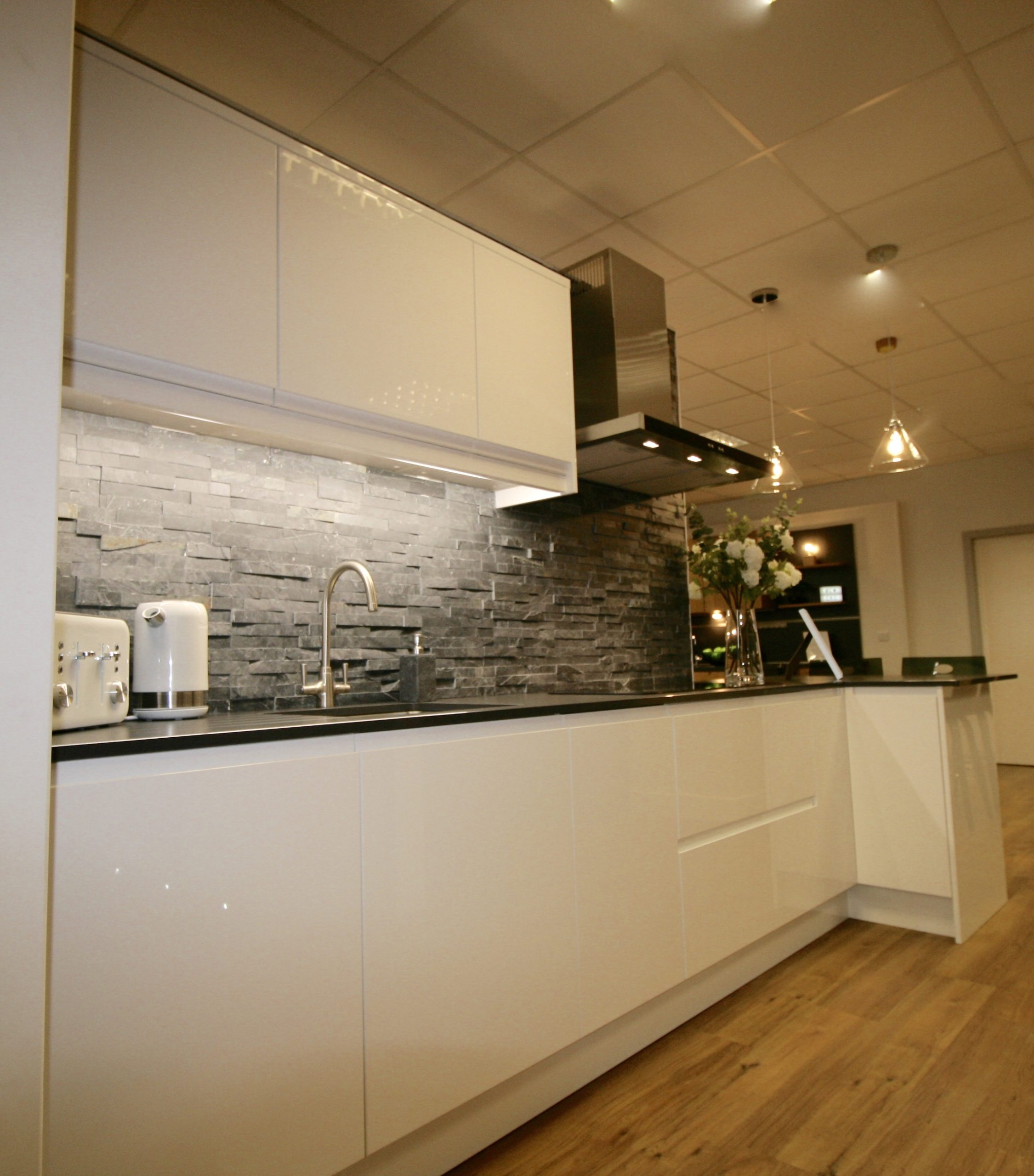 Remo high gloss white handleless kitchen by PWS with slate effect worktop and split face slate tiles.