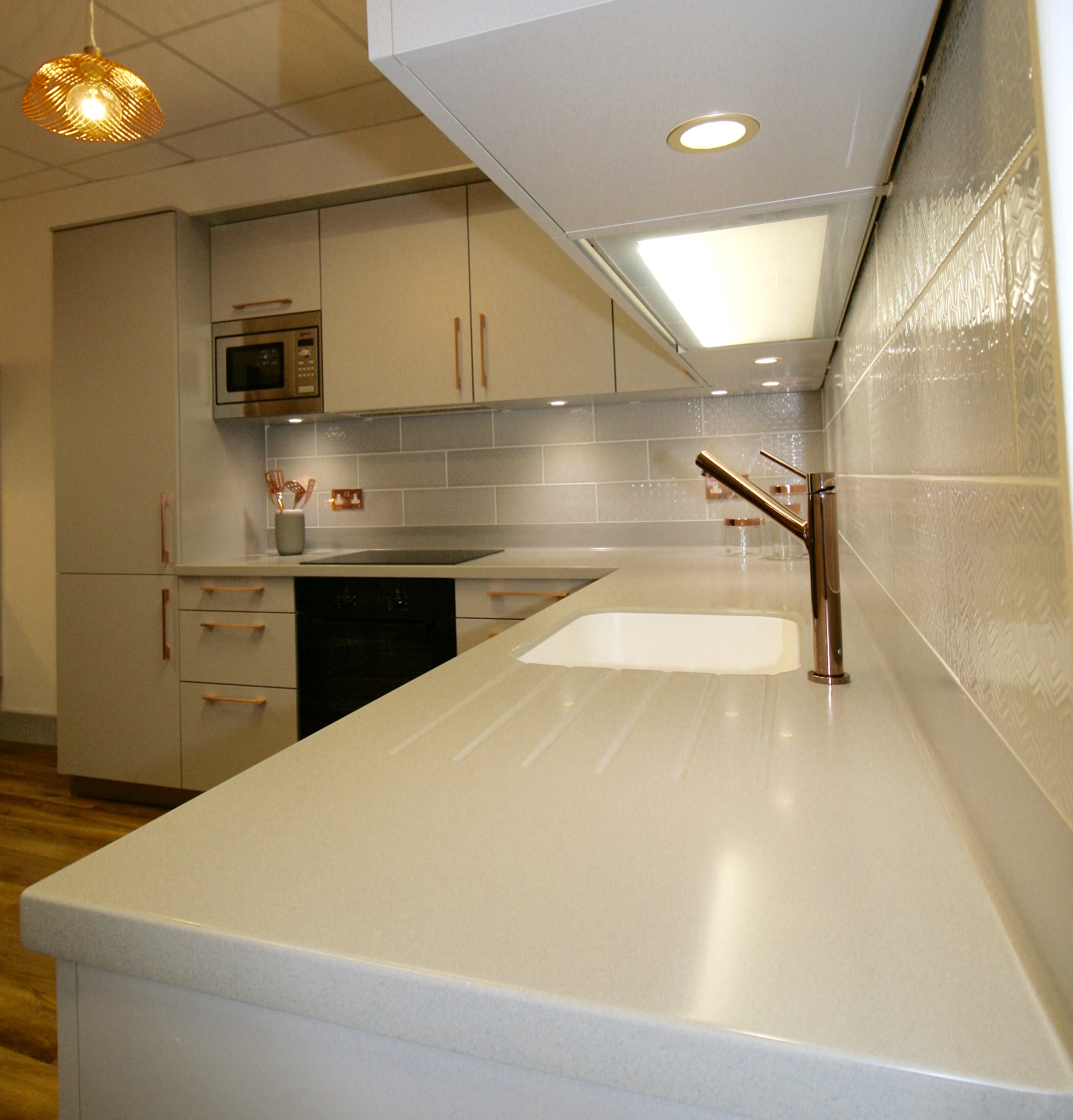 Dove grey Corian worktop with Designer White moulded sink and Avia polished copper tap