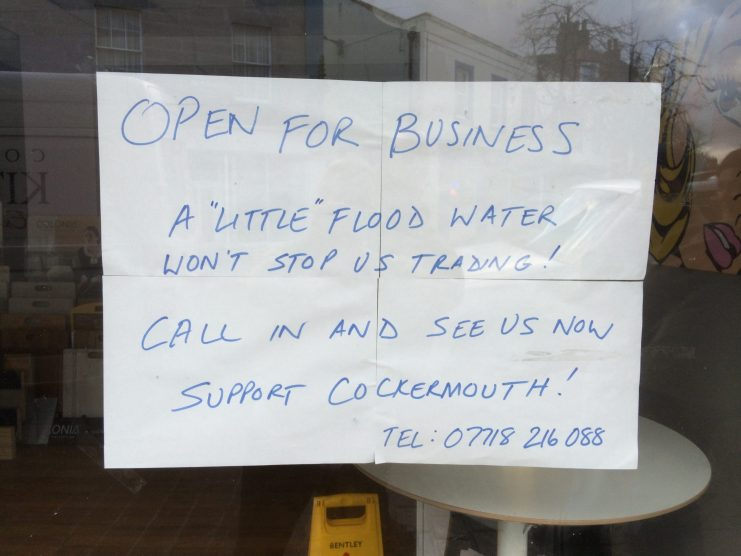 Sign in shop window in Cockermouth after Cumbria floods