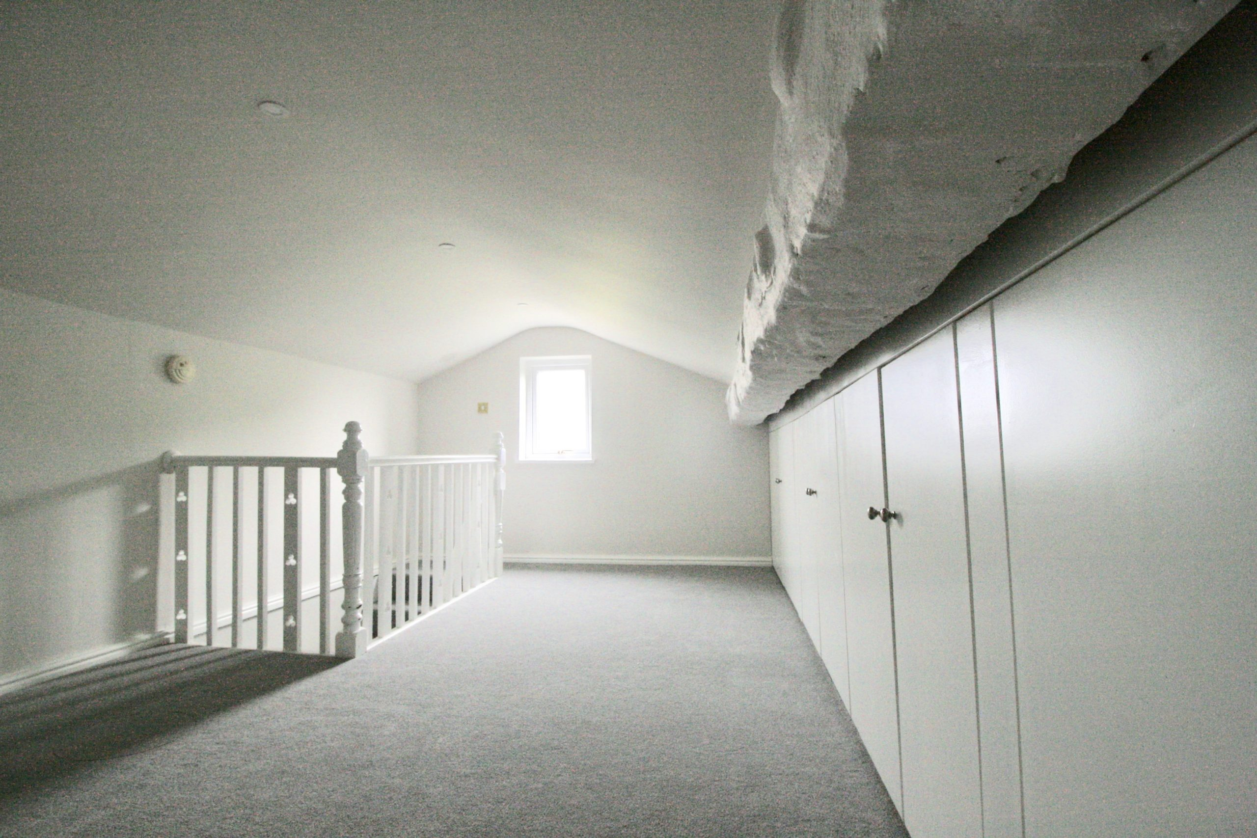 New office space with additional storage in loft space above TV room with grey and white decor