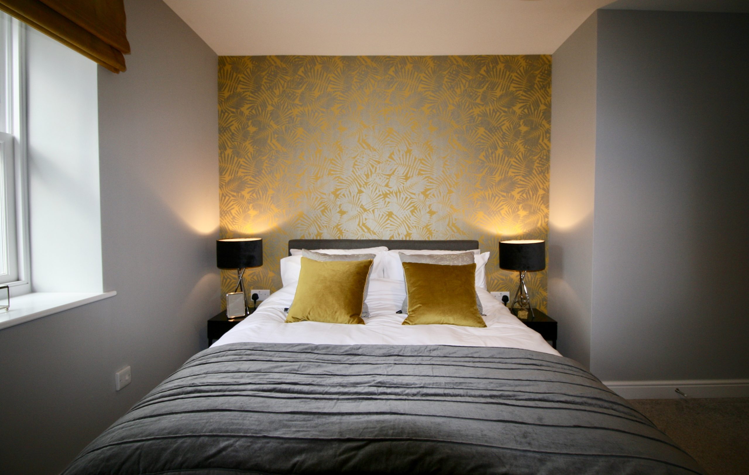 Mustard and charcoal grey fern wallpaper in master bedroom in show home