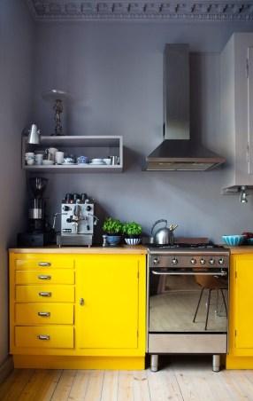 Yellow kitchen units in grey kitchen