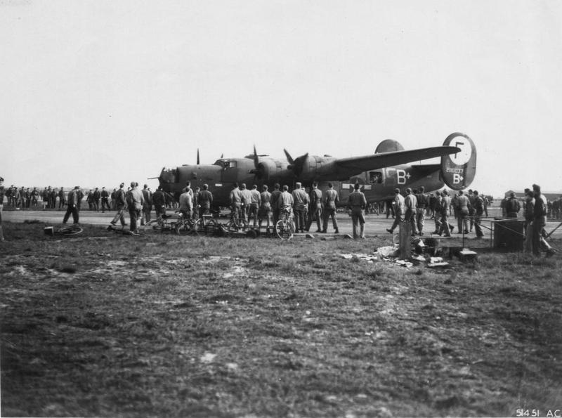 Ground personnel of the 445th Bomb Group gather around a B-24 Liberator (I5-B+, serial number 42-110037) after its return to base on D-Day. Printed caption on reverse: '51451- Ground crew swarming around a bomber returning from a D-Day mission for information on the invasion.' Handwritten caption on reverse: 'Lt Sam Miller's B-24 returning to Tibenham, Norfolk after he and crew completed a 25 mission tour of operations. First crew in the 445th bomb Group to do so.'