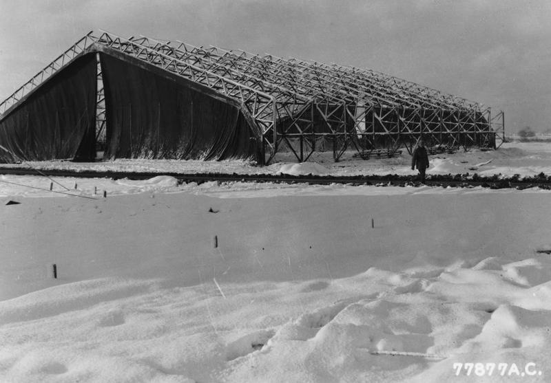 A hangar under construction at the 1st Tactical Air Depot at North Witham. Printed caption on reverse: '77877 AC - A butler hangar under construction by members of the 833rd Engineer Aviation Battalion at North Witham, England. U.S. Air Force Photo.'
