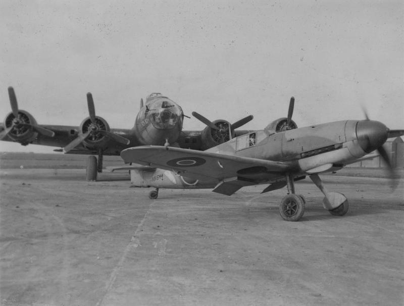 A captured RAF Messerschmitt Bf 109 (serial number NN 644) with a B-17 Flying Fortress of the 379th Bomb Group at Kimbolton, 8 January 1944. Passed for publication 8 Jan 1944. Handwritten caption on reverse: 'USAAF 36.' Printed caption on reverse: 'Strange Bedfellows. Associated Press Photo Shows:- Rivals in the air battles over Europe, a B-17 Flying Fortress and a German Me109, are here seen together at a U.S. Heavy Bomber Base