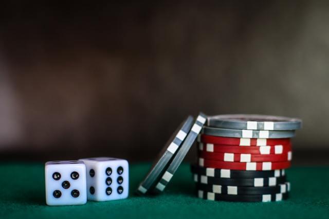 dadu dan chip poker di atas meja