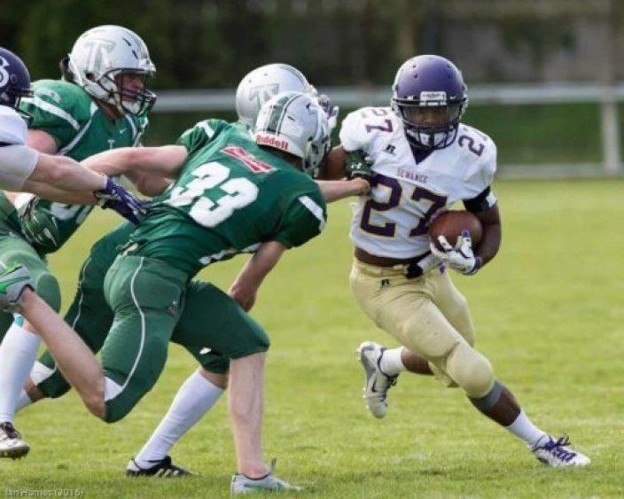 Running-Back Ronald Hayes Jr. evading Trojan defenders