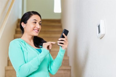a woman smiling holding her phone | American Home Services | Home Security Orlando