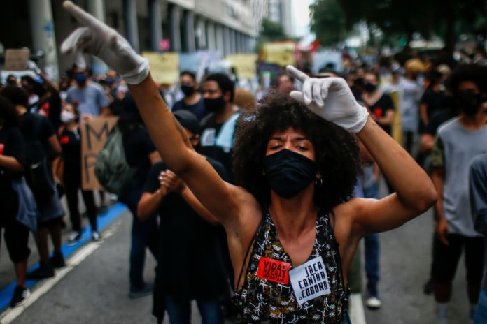 Afro-Brazilian protestor shouting angrily while wearing facemask