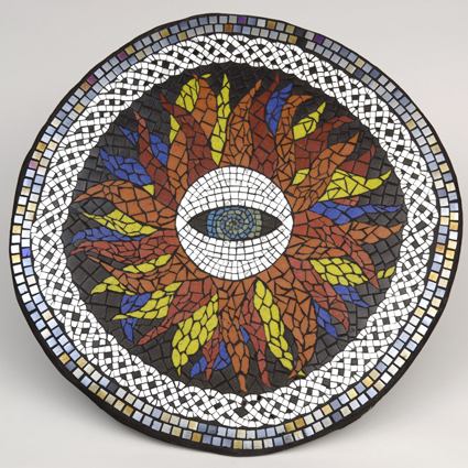 Image of a round glass mosaic table top featuring a central eye, fiery flames and a Celtic knot border in mirror tiles