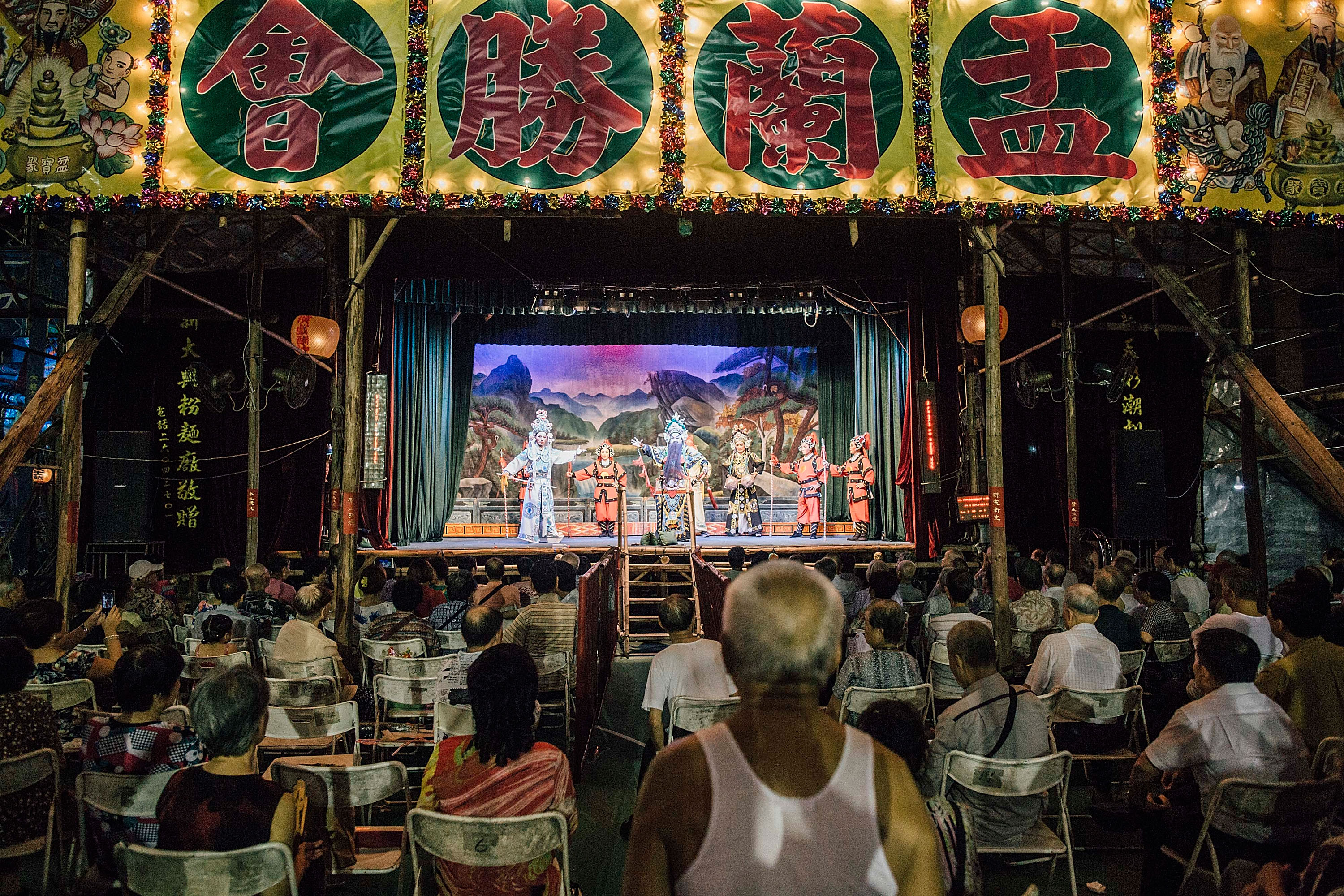 HONG KONG - AUGUST 14: Spectators watch a Chinese opera during the month of Hungry Ghost Festival (Yu Lan) on August 14, 2015 in Hong Kong. The Hungry Ghost Festival had been inscribed on to China?s third national list of intangible cultural heritage in 2011, is intrinsically linked to this Chinese practice of ancestor worship. The main activities for the festival includes paying respect to the ghosts, burning daily ware made with paper for the dead, opera for the spirits and bidding for lucky charm. (Photo by Anthony Kwan/For Hong Kong Images)
