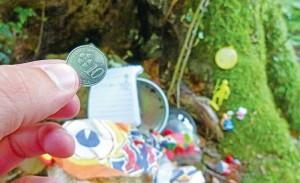Figurines, porte-clés, jouets, et même une pièce 10 Sen malaisiens composent cette cache trouvée sous une souche. - Photo GT