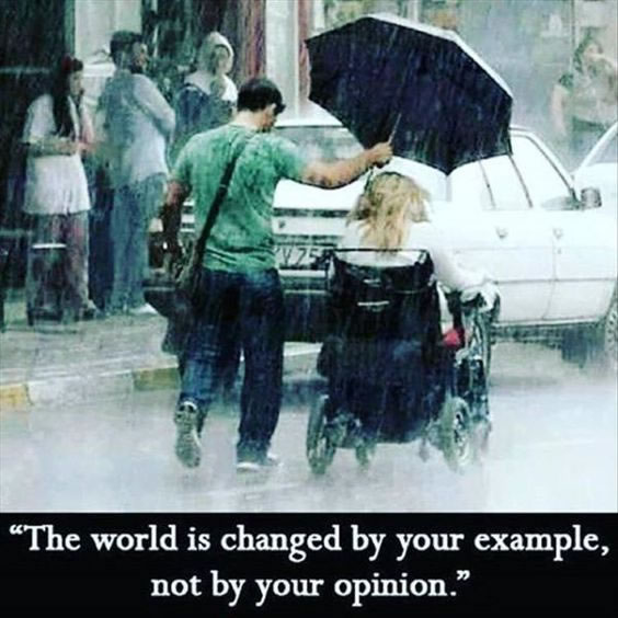 """Man holding an umbrella over a woman in a wheelchair. """"The world is changed by your example, not by your opinion."""""""