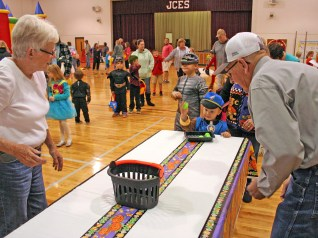 """Kendra Peek/kendra.peek@amnews.com Rowen Bragg, 2, """"bounces an eyeball"""" at the Junction City Elementary Fall Festival, with the help of Joyce, left, and Wilgus Pridemoore, right."""