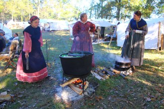 Reenactors from left, Elaine Orrand of Olive Branch, Mississippi, Karen Mynes of Barberton, Ohio, and Elaine Masciale of Palatine, Illinois, cook yarn in pots with natural dyes.