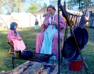 Barbara Myers of Tallahassee Florida sits with 7-year-old Katie in the living history village.