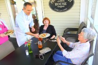 Ben Kleppinger/ben.kleppinger@amnews.com Mary Joe Bowling of Danville takes a photo of Gov. Matt Bevin as he serves her lunch on the porch of Grace Café Tuesday afternoon.