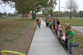 Kendra Peek/kendra.peek@amnews.com Junction City Elementary students line up while Rachalle Brandt does a cartwheel for the students on the sidewalk to the city park, one of the many projects volunteers with Lowe's Heroes and other community volunteers did for the school such as restriping the basketball court, painting the swings and more.
