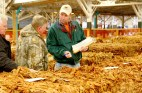 Jason Elliott with Farmers Tobacco Warehouse, right, talks with tobacco farmer Russell Skaggs as the two stand by bales of tobacco from Skaggs' farm that just sold at auction.