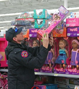 Kendra Peek/kendra.peek@amnews.com Danville firefighter Donnie Burke picks out a doll for a little girl during the Danville Fire Department Toy Drive.