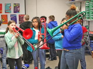 Kendra Peek/kendra.peek@amnews.com Jaden Owens, left, gets personal attention from Destiny Carter, right, on playing the trombone while other students look on. Owens is one of the fifth grade students at Hogsett Elementary School who have learned to play the trombone -- others learned to play the trumpet thanks to Conner Kinman.