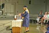 Kendra Peek/kendra.peek@amnews.com Jenny Beth Cox lights a candle during the Danville Christian Academy graduation on Saturday.