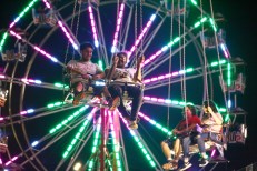The fair's ferris wheel backlights riders on another ride.