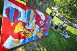 Festival-goers relax in the shade near a giant piece of Brass Band Festival art. (Photo by Ben Kleppinger)