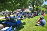 People relax in the shade as they listen to brass music on the main stage Saturday afternoon. (Photo by Ben Kleppinger)