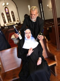 Father Chenille (Eben French Mastin) confronts Mother Superior (Patricia Hammond) with evidence that the nuns at the Sisters of Perpetual Sewing have been making wine without permission.