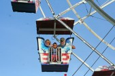 Kendra Peek/kendra.peek@amnews.com Maylee Woods, 4, center, rides the ferris wheel with her grandparents, Lisa Campbell, left, and Tommy Campbell, right.