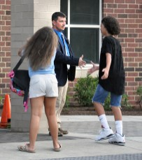 Toliver Elementary School principle Ron Ballard shakes hands with students as they enter on the first day of school.