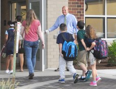 Ed McKinney, Director of Danville Schools Pupil Personnel, Buildings and Grounds and Transportation hold the door and welcomes students and families entering Toliver Elementary School on the first day of class.