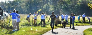 Volunteers of adults, teens and county officials work planting 100 different species of trees and bushes along Clark's Run behind Bate Wood Homes off of J.E. Woods Drive.
