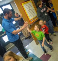 Jacob Tamme high-fives Cyrus Tipton and Jaelah Hellard they leave the Junction City Elementary gym Friday morning.