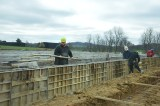Workers build and brace walls for concrete to be poured into.