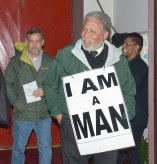 """J.H. Atkins enters Trinity Episcopal Church wearing an iconic """"I Am A Man"""" sign was worn in Memphis by sanitation workers who had been on strike 68 days. This was also the last protest that King joined. (Photo by Robin Hart)"""