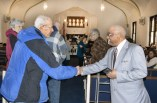 Arlen Finke, left, is greeted by pastor Ralph Smith at St. James A.M.E. Church. (Photo by Robin Hart)