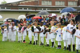 Kindergarten students stand in the rain before being called to the starting gate as spectators hover under umbrellas.