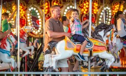 Zaidyn Williams, 2, waves to family as he rides the carousel with his grandfather, Joey Harris.
